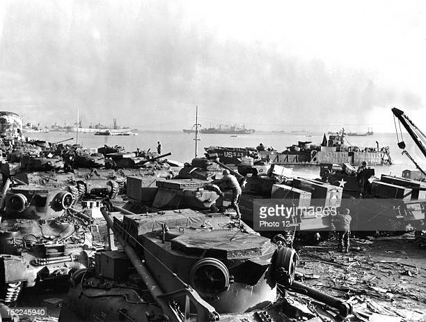 At Cherbourg harbor US ordnance crews swarm over newly arrived tanks part of a priority oder servicing them so that they can move on their own power...