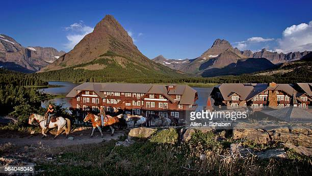 At dawn horses are brought to the ridge above Many Glacier Hotel for daily horesback rides around Swiftcurrent Lake at Glacier National Park in...