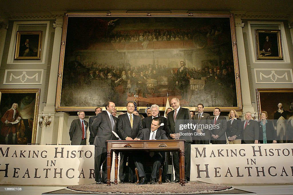 At Faneuil Hall, Gov. Mitt Romney signed a health care bill with many political figures present. Front row, from left to right: Timothy Murphy, Massachusetts Health & Human Services Secretary; Robert E. Travaglini, Senate President; Sen. Edward M Kennedy, Lt. Gov. Kerry Healey and Salvatore DiMasi, Speaker of Mass. State House of Representatives.