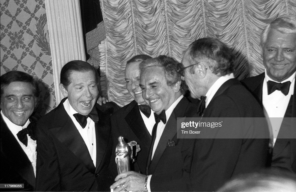 At Friars Club Testimonial Dinner in his honor, popular American performer <a gi-track='captionPersonalityLinkClicked' href=/galleries/search?phrase=Frank+Sinatra&family=editorial&specificpeople=70024 ng-click='$event.stopPropagation()'>Frank Sinatra</a> (1915 - 1998) (third left) receives a statuette from an assembled group including actor and comedian <a gi-track='captionPersonalityLinkClicked' href=/galleries/search?phrase=Milton+Berle&family=editorial&specificpeople=93778 ng-click='$event.stopPropagation()'>Milton Berle</a> (1908 - 2002) (second left), Friars Club Dean Buddy Howe (1910 -1981) (third right), television executive David Tebet (1913 - 2005) (second right), and British-born American actor Cary Grant (born Archibald Leach, 1904 - 1986) (right), at the Waldorf Astoria, New York, New York, February 1976.