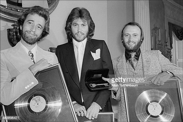 At Gracie Mansion for an awards ceremony and luncheon music group the Bee Gees Robin Barry and Maurice Gibb pose with gold records and the Key to New...