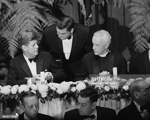 At Hilton Hotel President John F Kennedy sits with Dr Arthur Lee Kinsolving president of the Protestant Council of New York as Press secretary Pierre...