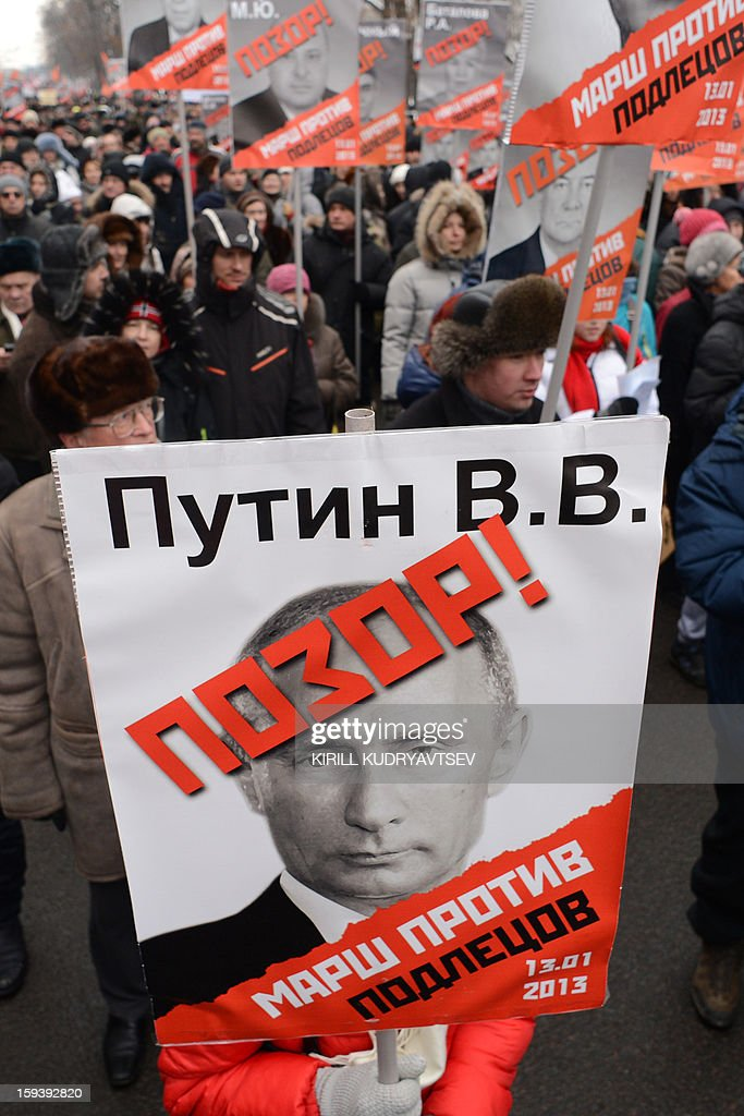 At least 20,000 Russian opposition supporters rally on January 13, 2013 with placards bearing photos of President Valdimir Putin on the Boulevard Ring in the center of Moscow against a Kremlin law that banned US adoptions of Russian orphans. The protest dubbed 'the March Against Scoundrels' was aimed at naming and shaming the lawmakers who fast-tracked the anti-adoption bill through the lower house parliament, the State Duma.