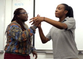 At left Porsha Olayiwola Codman Academy team coach works with student Ogechi Okwologu during practice for the upcoming team poetry slam competition...