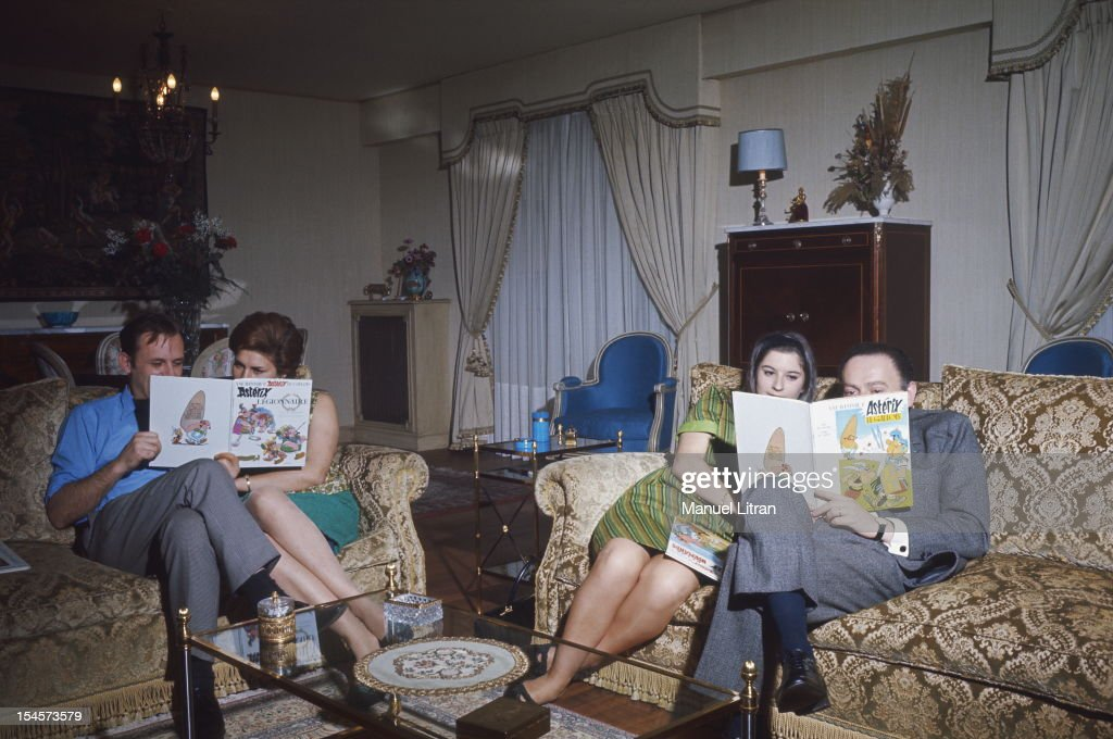 sitting on sofas in the lounge, from left to right, Albert Uderzo and his wife Ada, Gilberte and her husband Rene Goscinny, all four dive into the adventures of Asterix.