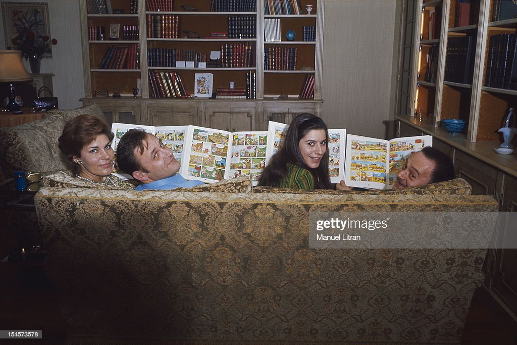 sitting on the couch, from left to right, Ada and her husband Albert Uderzo, Gilberte and her husband Rene Goscinny, all four smiling. Gilberte and Ada are the first to know the new adventures of Asterix.