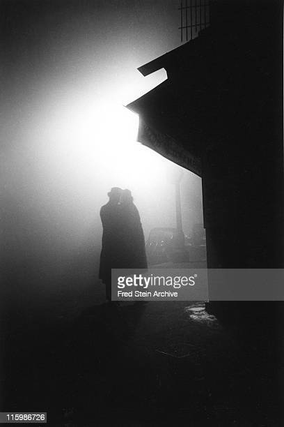 At night a couple embrace in the darkness of a foggy street corner Paris France 1934