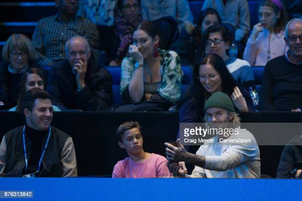 A fan gets a selfie with David Beckham while son Romeo looks on during the Mens final between David Goffin and Grigor Dimitrov at O2 Arena on...