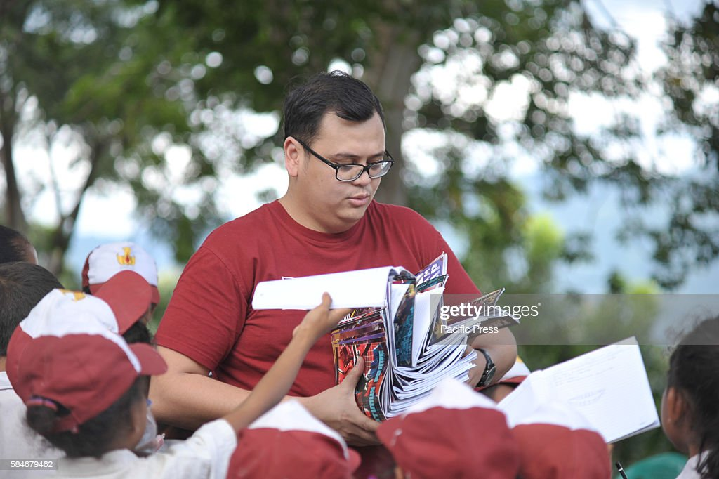 At one of Indonesia's oldest catholic schools a voluntary teacher from Sekolah Pelita Harapan holds students' work books Each year the student...