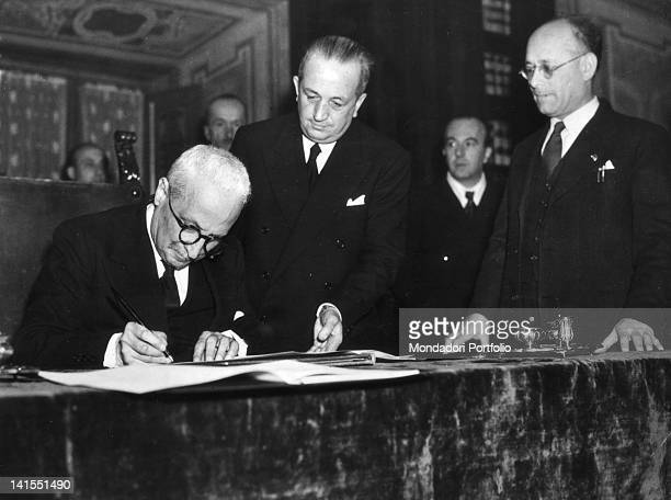 At Palazzo Giustiniani the President of the Italian Republic Enrico De Nicola is signing the Constitution assisted by the Speaker of the Constituent...