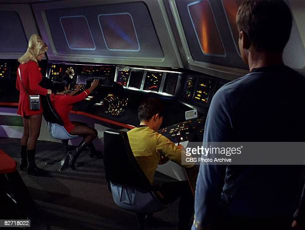 At right American actor DeForest Kelley stands behind American actor George Takei and watches actresses Grace Lee Whitney and Nichelle Nichols in a...