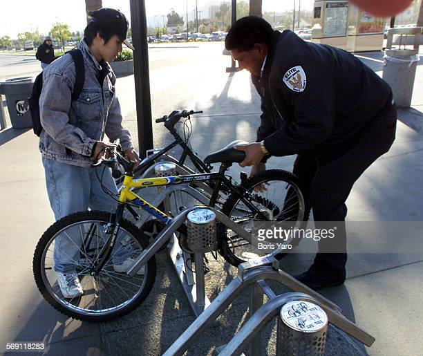 at Right is MTA security guard Policarpo Gomez in blue coat helping subway rider Peter Napoles of Sherman Oaks lock his bike in a rack prior to...