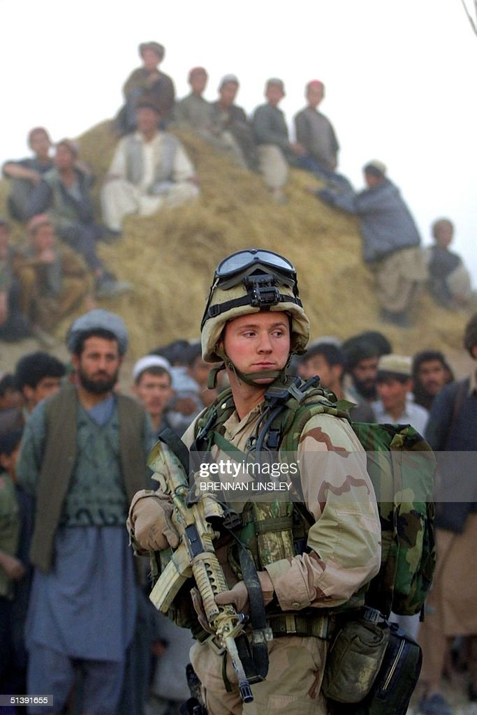 At sundown a United States Special Forces soldier stands guard near a helicopter as Afghan civilians and militiamen loyal to the rebel Northern...