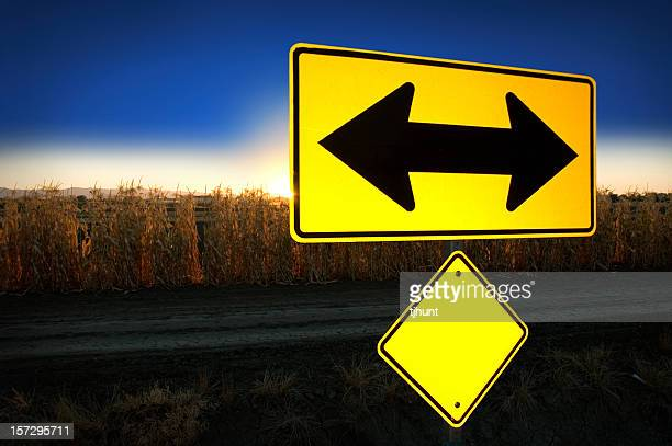 At sunset, two-way road sign with corn