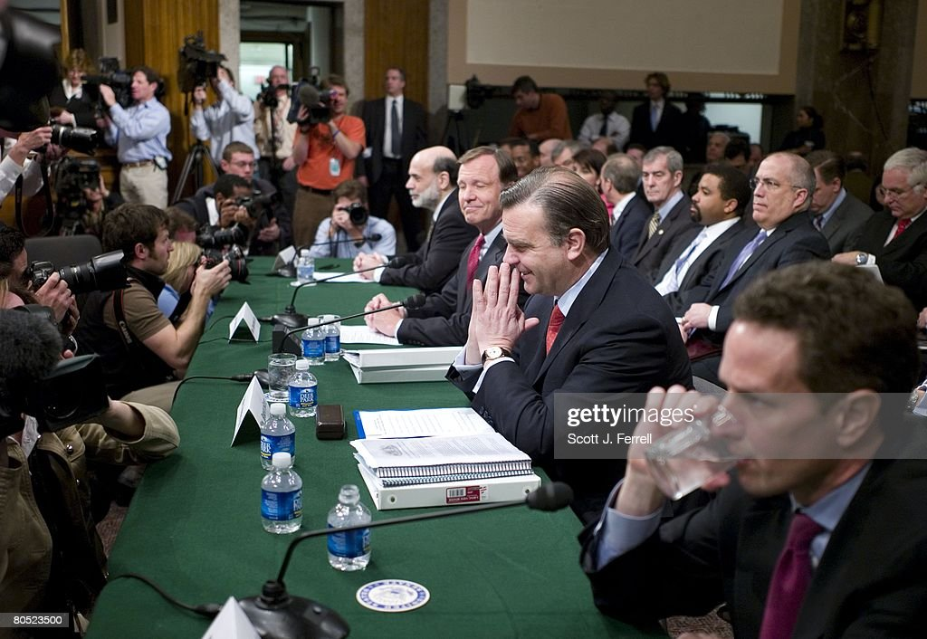 At table background foreground Federal Reserve Board Chairman Ben S Bernanke Securities and Exchange Commission Chairman Christopher Cox Treasury...