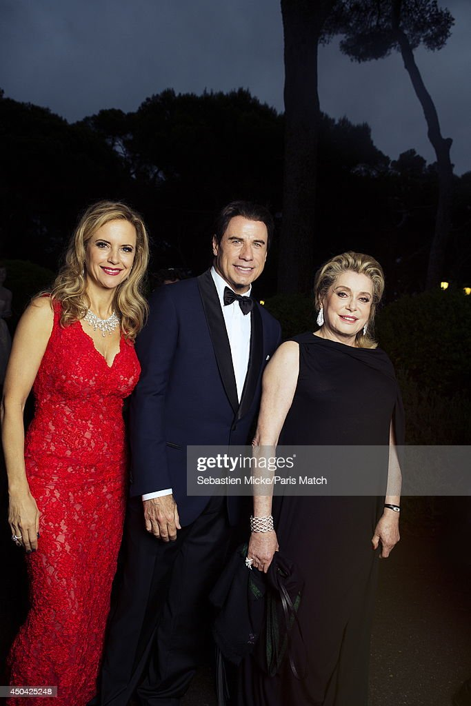 at the 21th Gala of AmFar Cinema Aganist AIDS, <a gi-track='captionPersonalityLinkClicked' href=/galleries/search?phrase=John+Travolta&family=editorial&specificpeople=178204 ng-click='$event.stopPropagation()'>John Travolta</a> with his wife <a gi-track='captionPersonalityLinkClicked' href=/galleries/search?phrase=Kelly+Preston&family=editorial&specificpeople=159434 ng-click='$event.stopPropagation()'>Kelly Preston</a> wearing a Olivier Tolentino Couture dress and <a gi-track='captionPersonalityLinkClicked' href=/galleries/search?phrase=Catherine+Deneuve&family=editorial&specificpeople=123833 ng-click='$event.stopPropagation()'>Catherine Deneuve</a> wearing Vionnet dress with Boucheron jewelry are photographed for Paris Match in Cap d'Antibes at the Hotel Cap-Eden-Roc on May 22, 2014;