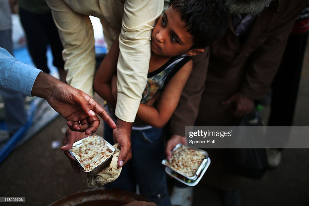 At the base for Mohamed Morsi supporters, a boy waits in line to receive food in order to break the days fast on the first day of Ramadan, the sacred holy month for Muslims where many will fast from sun-up to sun-down on July 10, 2013 in Cairo, Egypt. Egypt continues to be in a state of political paralysis following the ousting of Muslim Brotherhood leader Mohamed Morsi by the military. Adly Mansour, chief justice of the Supreme Constitutional Court, was sworn in as the interim head of state in a ceremony in Cairo on the morning of July 4.