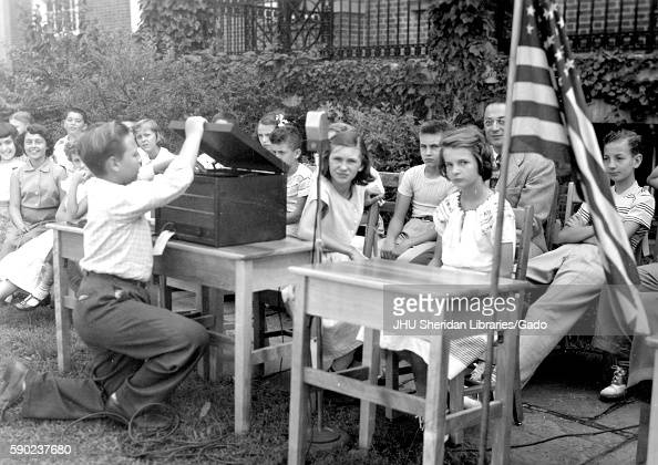 At the closing day activities for an elementary demonstration school at Johns Hopkins University students sit at chairs in a row while one classmate...
