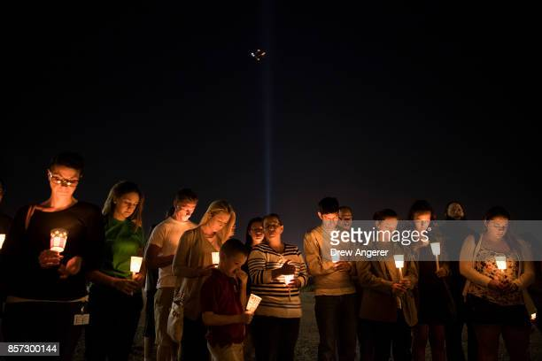At the corner of Sunset Road and Las Vegas Blvd mourners attend a candlelight vigil for the victims of Sunday night's mass shooting October 3 2017 in...