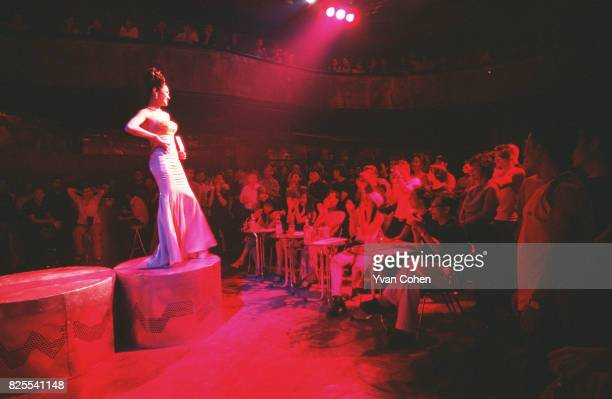 At the end of the catwalk a transsexual strikes a final pose for the audience and judges during a beauty contest at a nightclub in downtown Bangkok