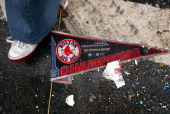 At the end of the parade on Tremont Street near the Boston Common a dropped pennant lies on the ground as the crowds disperse following the rolling...