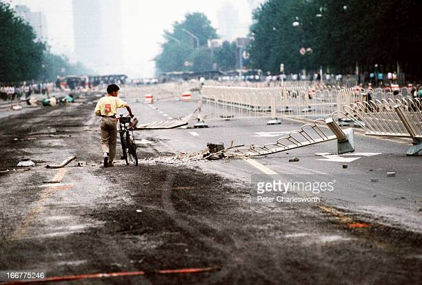 At the end of the prodemocracy movement in China a lone cyclist walks past street barriers on Changan Avenue crushed by Chinese Army tanks during the...