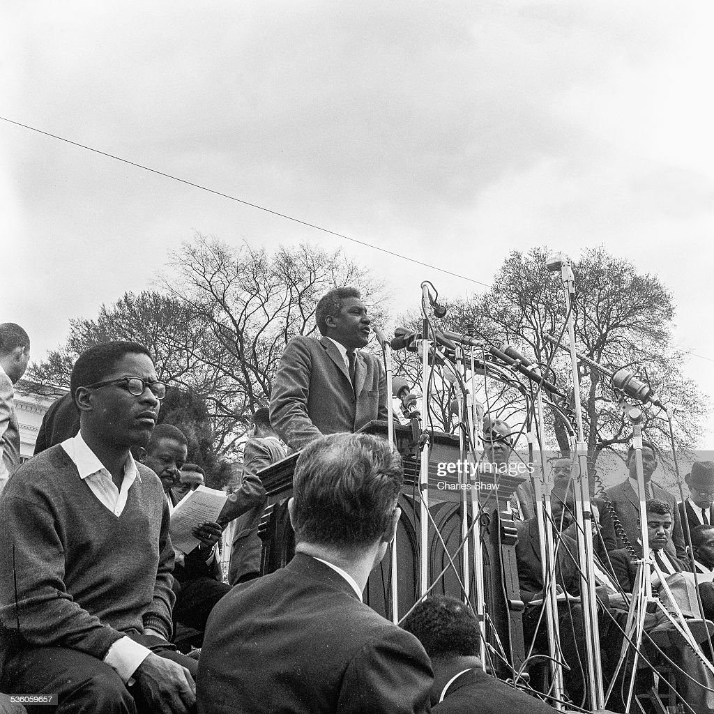 At the end of the Selma to Montgomery March, Civil Rights leader Bayard Rustin (1912 - 1987) speaks to the assembled marchers and spectators in front of the Alabama State Capitol, Montgomery, Alabama, March 25, 1965. At left (in v-neck sweater) is Bernard Lee (1935 - 1991) of the Student Non-Violent Coordinating Committee, and behind him is Ralph Abernathy (1926 - 1990) reviewing his notes. The pulpit is from the Dexter Avenue Baptist Church, and it is the one that Martin Luther King Jr preached his sermons when he was pastor between 1954 to 1960.