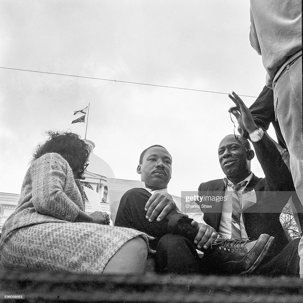 At the end of the Selma to Montgomery March, Coretta Scott King (1927 - 2006), Martin Luther King Jr (1929 - 1968), and an unidentified man talk on the podium in front of the Alabama State Capitol, Montgomery, Alabama, March 25, 1965. The Confederate and Alabama flags fly over the Capitol.