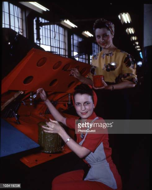 At the homefront women aircraft workers apply finishing touches to the paintwork of a Curtiss SB2C 'Helldiver' wing section at the Hudson Motor Car...