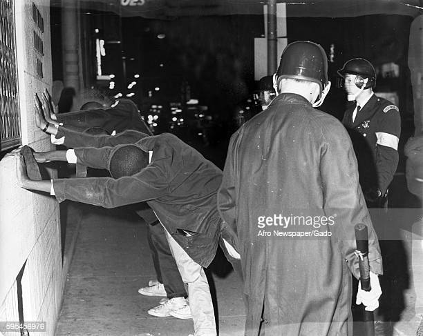 At the intersection of Bradford and Lanvale streets in Baltimore Maryland Caucasian riot policemen holding billy clubs and helmets check suspected...