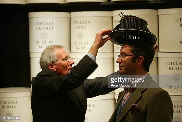 At the James Lock Co an unidentified man is fitted with a conformateur by a hat maker London England October 12 2004
