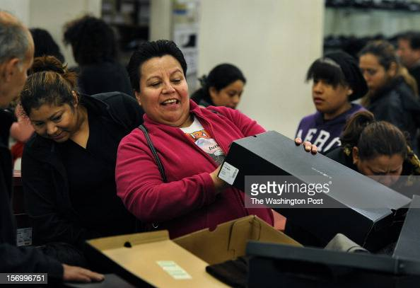 At the JC Penney store Imelda Diaz of Landover MD checks to find her size for some boots that normally sell for $6500 but were on sale for $2500 She...