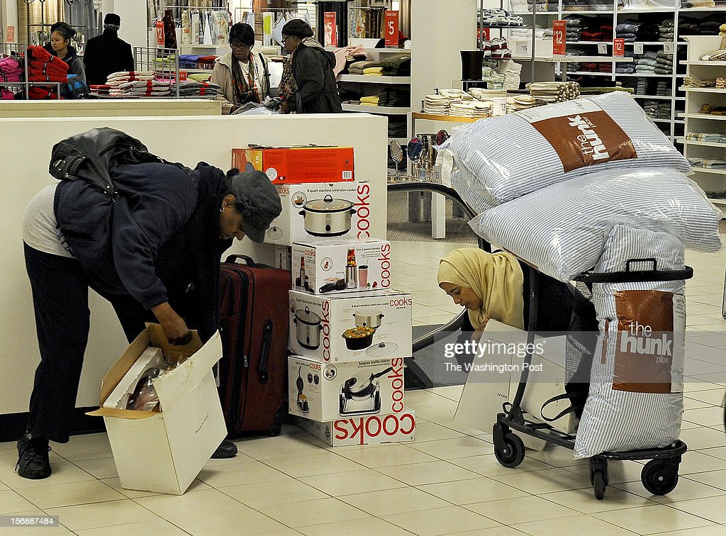 At the J.C. Penney store, (L) Velita Smith bought a suitcase and a host of kitchen items for her mother who is remodeling her kitchen. She checks a toaster oven that was opened. The items were on sale for $8.00 each - a savings of about 70% for many items. At right is Sozi Yousuf who is loading her toaster ovens and King size pillows she bought for $3.00 each. She came just for the great prices as her family does not celebrate Christmas. The J.C. Penney store opened at 6:00 am today in hopes that a Black Friday rush will help sales that have been sluggish of late. (Photo by Michael S. Williamson/The Washington Post via Getty Images
