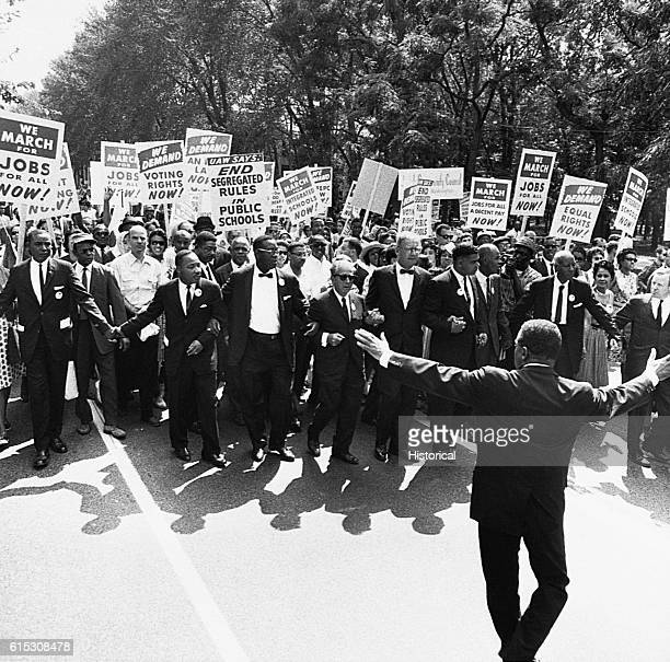 At the March on Washington for Jobs and Freedom attended by an estimated 200000 people a group heads down a street carrying protest signs Dr Martin...
