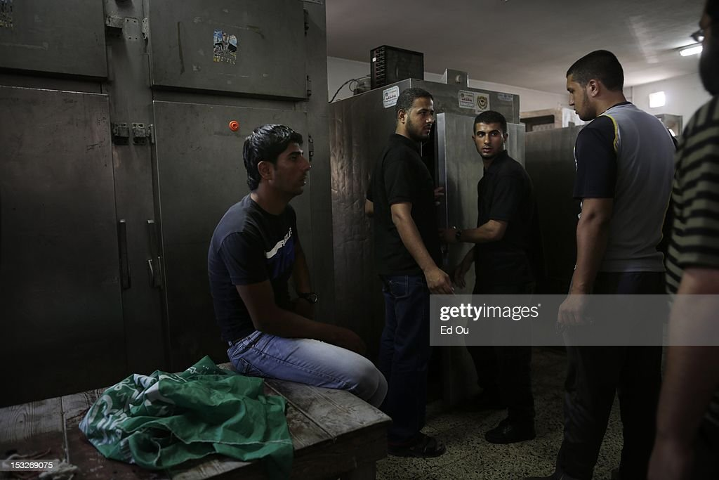 At the morgue in Shifa Hospital in Gaza City, relatives stand around the refrigerator holding the body of Palestinian militant Zakareya al-Jammal, 21, who was killed by Israeli fire as he was preparing to launch rockets into Israel on Sept. 6, 2012. He was the son of prominent Hamas commander Abu Zakaria al-Jamal, who was killed during Israel's Operation Cast Lead.