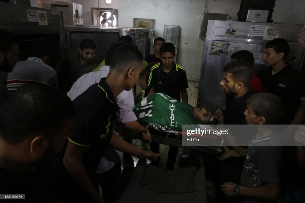 At the morgue in Shifa Hospital in Gaza City, relatives stand over the body of Palestinian militant Zakareya al-Jammal, 21, who was killed by Israeli fire as he was preparing to launch rockets into Israel on Sept. 6, 2012. He was the son of prominent Hamas commander Abu Zakaria al-Jamal, who was killed during Israel's Operation Cast Lead.