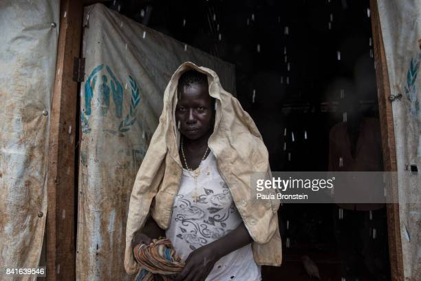 At the Nyumanzi transit camp a woman stands outside a large tent as the rains cause further problems for the refugees The Onward Struggle A refugee...