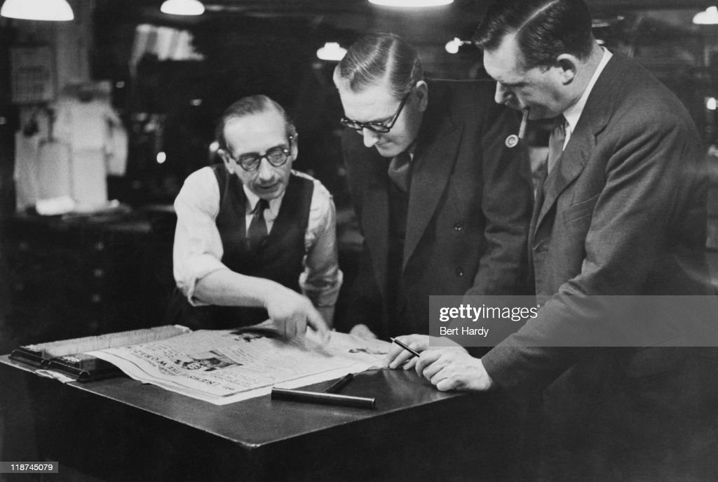 At the offices of the News of The World, Deputy Editor Reg Cudlipp (1910 - 2005, centre) and Chief sub-editor 'Tiny' Lear (right) settle a problem on the 'stone', the wheeled table holding the page of type, April 1953. Original Publication : Picture Post - 6488 - The News of The World - pub. 18th April 1953.