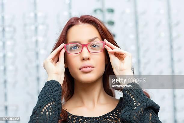 Dans l'optique jeune femme choisit des lunettes Ophthalmology boutique d'optique