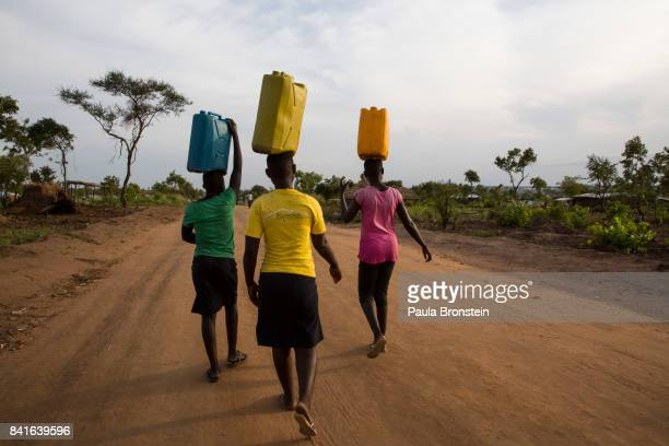 At the Pagarinya camp women carry water back to her tents The Onward Struggle A refugee crisis in Uganda deepens as South Sudanese Refugees are...