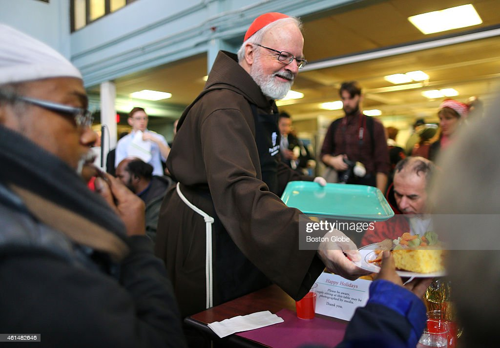 At the Pine Street Inn, Cardinal Sean O'Malley, along with gov-elect Charlie Baker and Lt. Gov. elect Karen Polito greeted the homeless at the shelter where the Cardinal said a prayer before they all served the Christmas Eve luncheon to the homeless in the dining room. O'Malley hands a meal to the table.