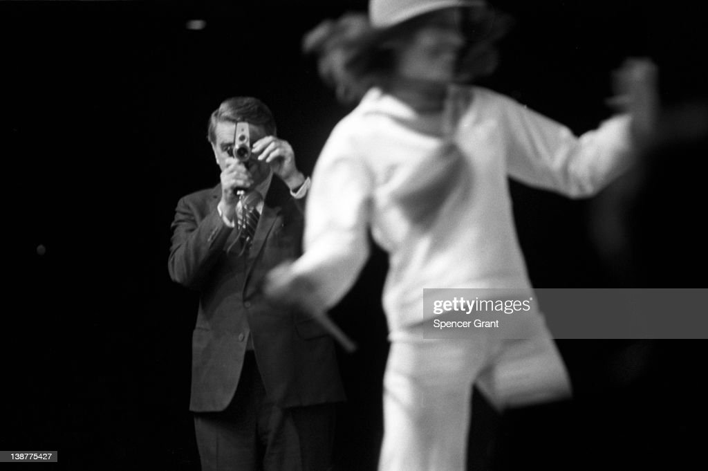 At the Polaroid Corporation annual meeting, President Edwin H. Land demonstrates his company's Polavision instant movie camera with the help of a dancer, Boston, Massachusetts, 1977.