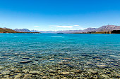The Southern Alps behind crystal-clear Lake Tekapo, New Zealand