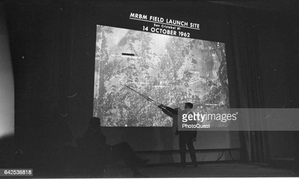 At the State Department an unidentified man points out a location on a projected slide during a presentation Washington DC October 14 1962 The slide...