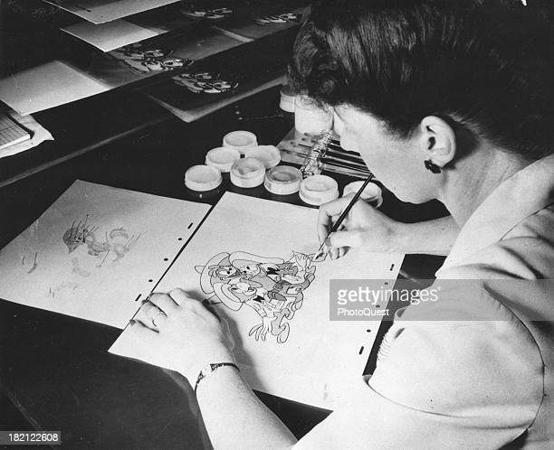 At Walt Disney Studios an unidentified animator an unidentified colorist in the Ink and Paint Division works on a drawing of Donald Duck California...