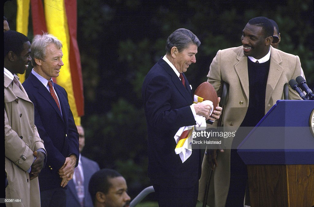 At White House ceremony honoring Super Bowl champion Doug Williams of the Washington Redskins President Ronald W Reagan receives a football and...
