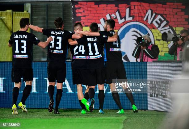 Atalanta players congratulate teammate defender Andrea Conti after scoring during the Italian Serie A football match Atalanta vs Juventus at the...