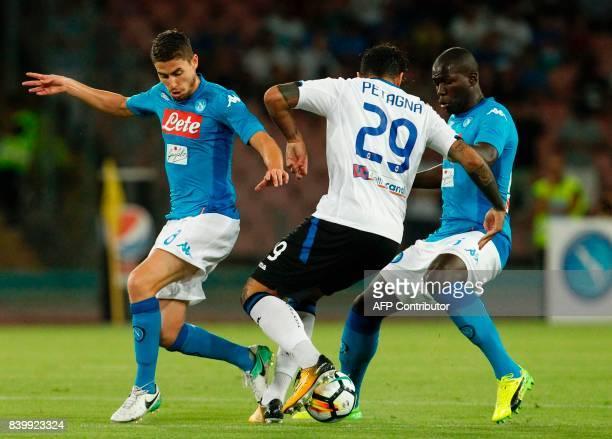 Atalanta'a Italian forward Andrea Petagna fights for the ball with Napoli's French defender Kalidou Koulibaly and Napoli's Italian midfielder...