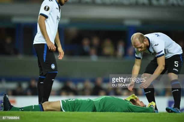 Atalanta's Albanian goalkeeper Etrit Berisha lies ijured after a clash with Everton's Spanish striker Sandro Ramirez during the UEFA Europa League...