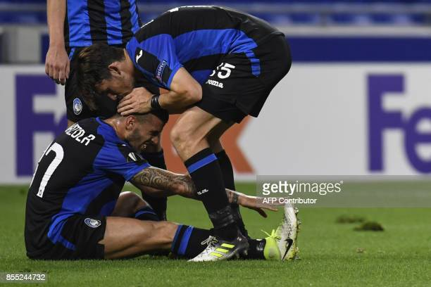 Atalanta's Italian defender Leonardo Spinazzola and teammate Italian defender Mattia Caldara react at the end of the Europa League football match...